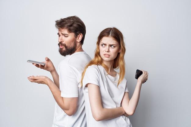 Família de homem e mulher com telefones nas mãos, estilo de vida de estúdio de comunicação
