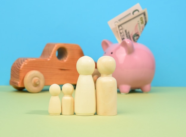 Família de homenzinhos de madeira fica no fundo do porco cofrinho e carro de madeira, conceito de economia de dinheiro