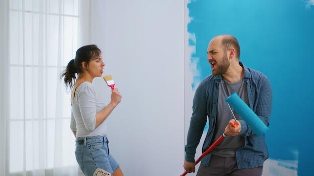 Família de jovem feliz cantando na escova de rolo enquanto fazia uma reforma no apartamento. redecoração de apartamento e construção de casa durante a reforma e melhoria. reparação e decoração.