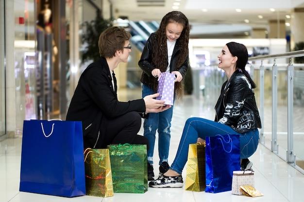 Família de jovem feliz com sacos de papel, compras no shopping. vitrines com roupas