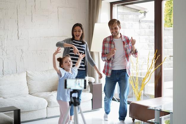 Família de jovem feliz dançando em casa com sua filhinha fofa, gravando um vídeo.