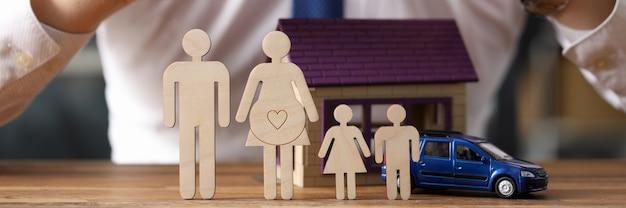 Família de madeira silhueta contra agente de seguros