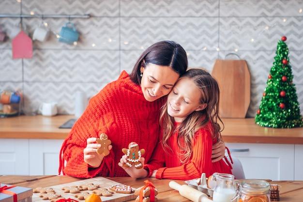 Família de mãe e filha com biscoitos de natal na cozinha