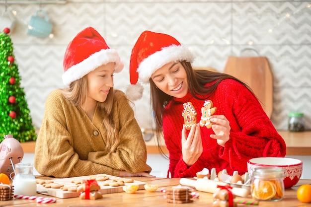 Família de mãe e filha com chapéu de papai noel preparando biscoitos de natal na cozinha
