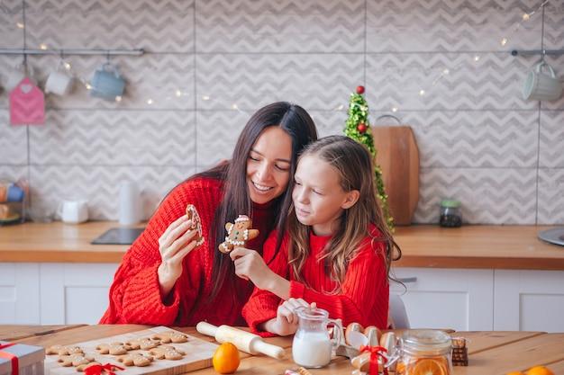 Família de mãe e filha cozinhando biscoitos de natal juntos em casa. feliz natal e boas festas.