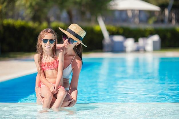 Família de mãe e filha curtindo férias de verão na piscina de luxo