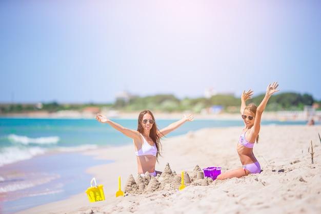 Família de mãe e filha fazendo castelo de areia na praia branca tropical