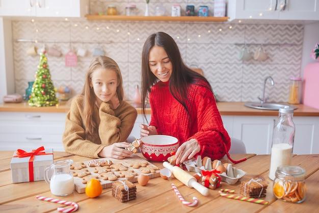 Família de mãe e filha preparando biscoitos de natal na cozinha