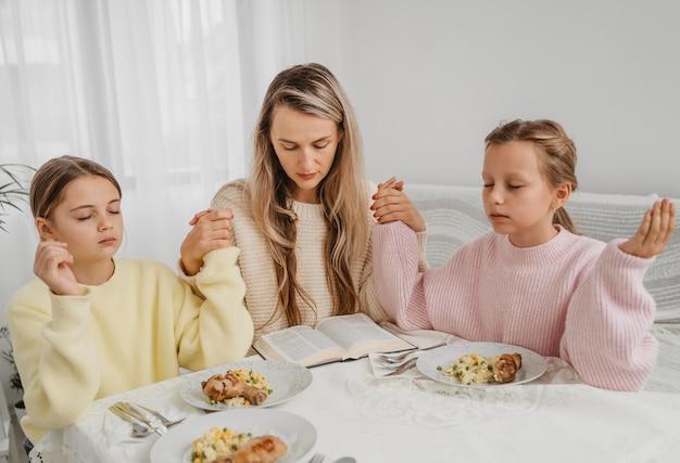 Família de mãe e filhas rezando à mesa de jantar