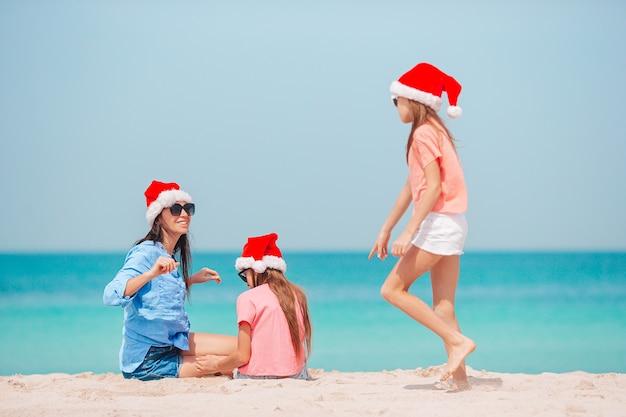 Família de mãe e filhos com chapéu de papai noel nas férias de natal na praia
