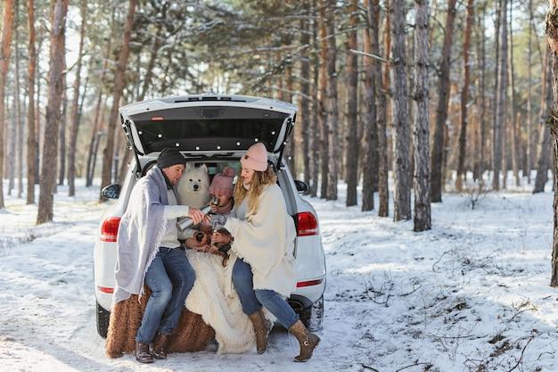 Família de mãe, pai e filha em jaquetas quentes e um engraçado cão samoyed branco