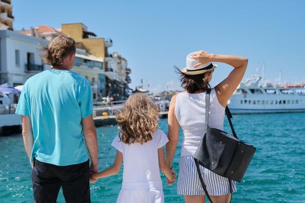 Família de mãos dadas, vista traseira, férias no mar mediterrâneo.