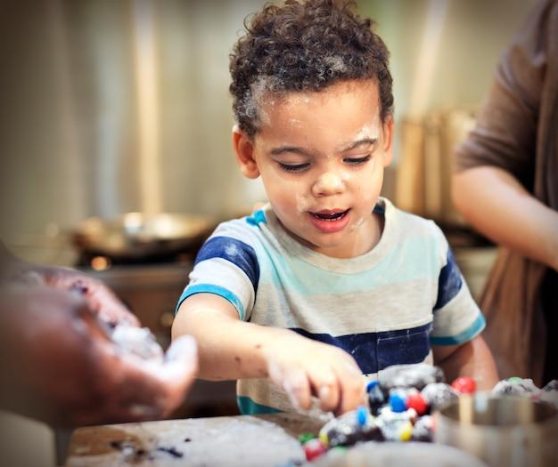 Família de menino pequeno que coze o conceito caseiro do bolinho