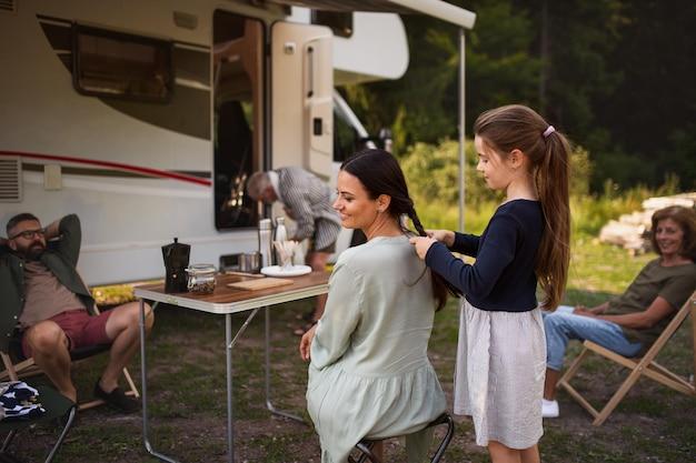 Família de multi-geração feliz sentado e falando de carro, viagem de férias de caravana.