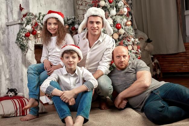 Família de natal. felicidade. retrato de pai, mãe e filhos de diferentes idades estão sentados no sofá em casa perto da árvore de natal e lareira, todo mundo está sorrindo.