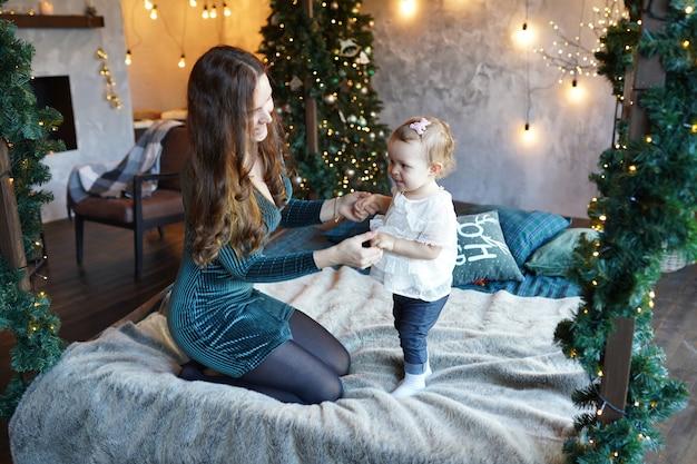Família de natal, jovem mãe e sua filha se divertir na decoração do quarto com luzes e árvore de natal, conceito de férias