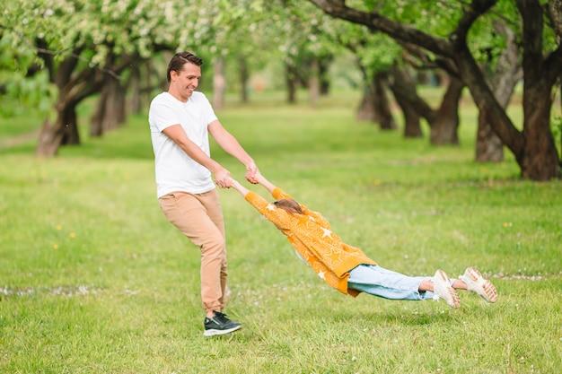 Família de pai e filha no jardim de cerejeira desabrocham