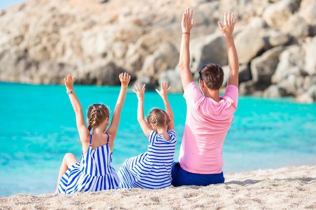 Família de pai e filhos na praia de areia branca i