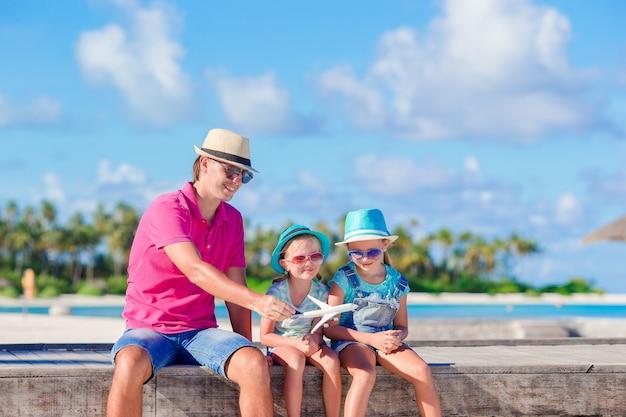 Família de pai e filhos na praia de areia branca