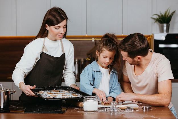 Família de pai e mãe com filha cozinhando juntos em casa