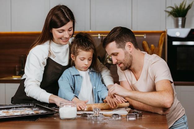Família de pai e mãe com filha cozinhando juntos
