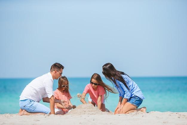 Família de pais e filhos brincando com areia em uma praia tropical