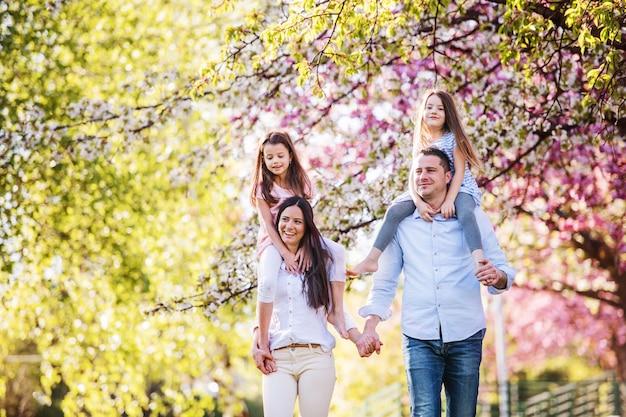 Família de pais jovens com pequenas filhas caminhando ao ar livre na natureza da primavera.