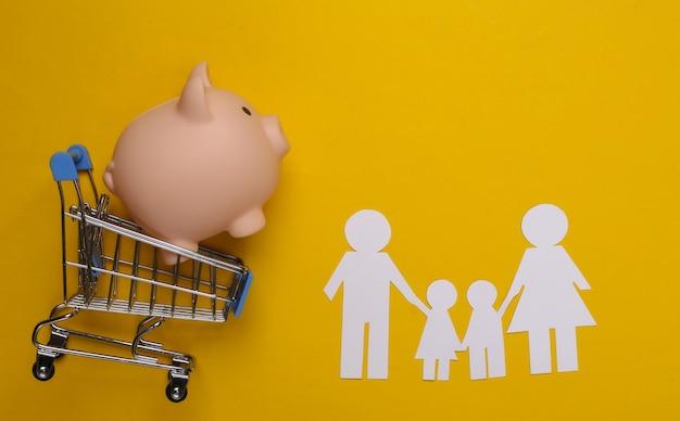 Família de papel junta e carrinho de supermercado com cofrinho em um amarelo. compras em família.