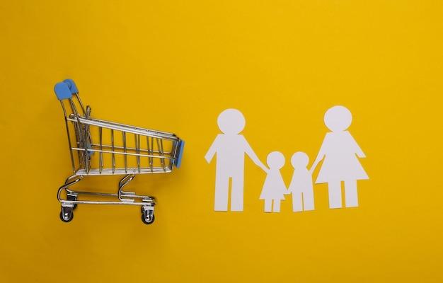 Família de papel junta e carrinho de supermercado em um amarelo. compras em família.
