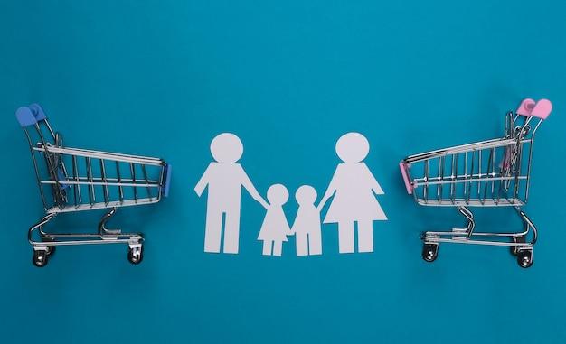 Família de papel junta e carrinhos de supermercado em azul. compras em família.