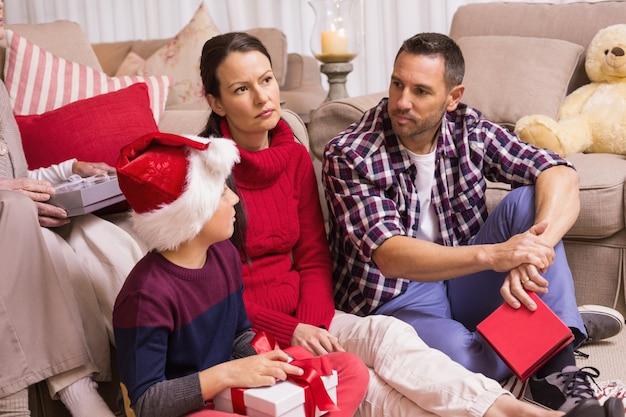 Família de pensamento sentado e segurando presentes