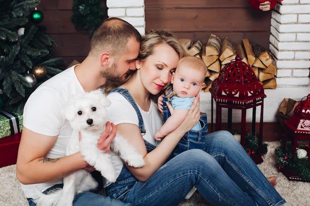 Família de positividade posando juntos perto da lareira e presentes para o natal