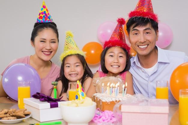 Família de quatro com bolo e presentes em uma festa de aniversário