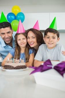 Família de quatro com bolo e presentes na festa de aniversário