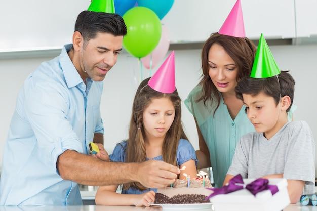 Família de quatro com bolo em uma festa de aniversário