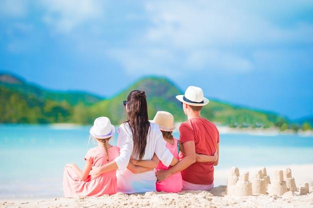Família de quatro fazendo castelo de areia na praia tropical branco