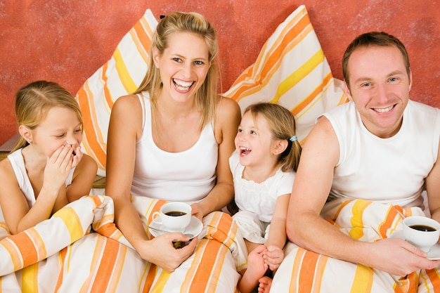 Família de quatro na cama tomando café da manhã