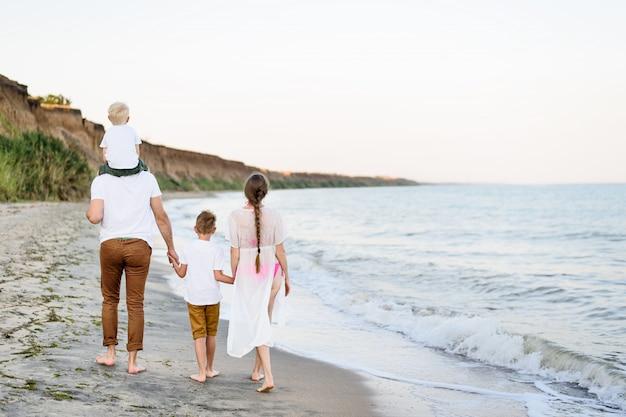 Família de quatro pessoas caminhando à beira-mar. pais e dois filhos. vista traseira