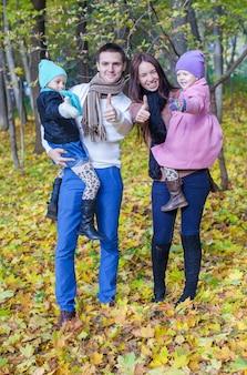 Família de quatro pessoas curtindo férias de outono e mostrando um polegar para