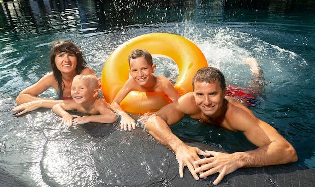 Família de quatro pessoas curtindo um dia na piscina juntos