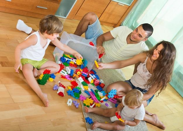 Família de quatro pessoas em casa com brinquedos