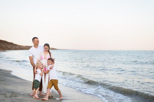 Família de quatro pessoas feliz abraçando na costa do mar. pais, mãe grávida e dois filhos.