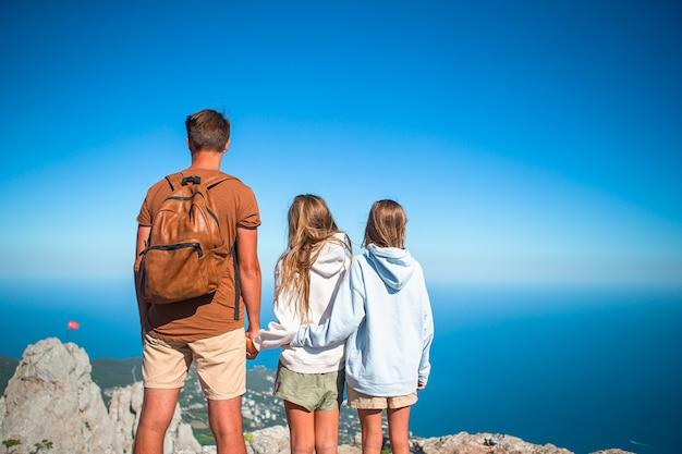Família de quatro pessoas feliz caminhando nas montanhas