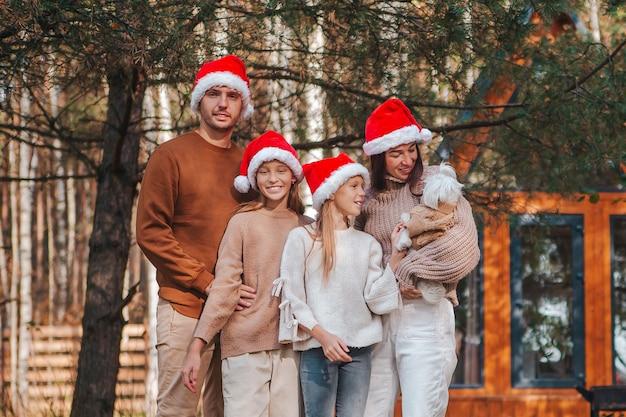 Família de quatro pessoas feliz com chapéu de papai noel aproveitando as férias de natal