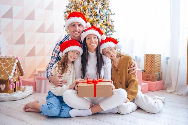 Família de quatro pessoas nas férias de natal em casa. feliz natal e boas festas.
