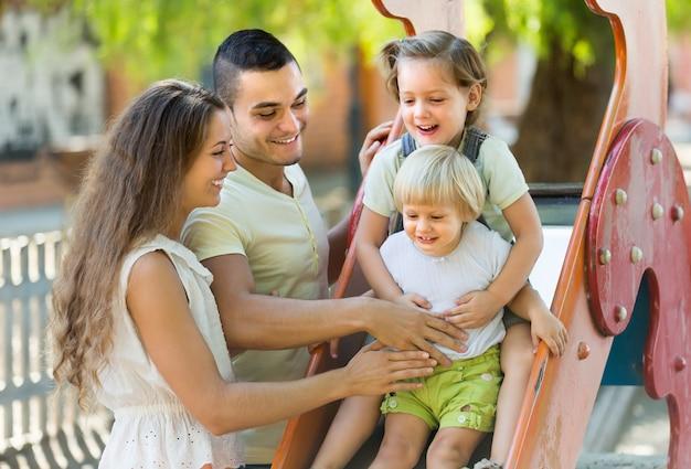 Família de quatro pessoas no parque infantil