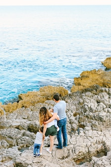 Família de quatro pessoas olhando para o mar em uma praia rochosa em montenegro