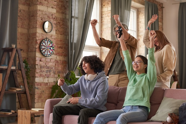 Família de quatro pessoas se divertindo juntos jogando videogame em casa