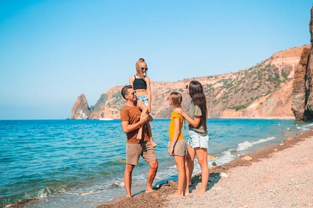 Família de quatro pessoas se divertindo na praia