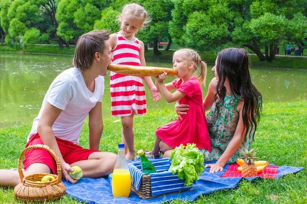 Família de quatro pessoas têm piquenique no parque no dia de verão